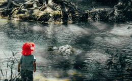 Ung pojke på foten av floden fotografering för bildbyråer