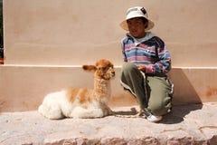 Ung pojke posera med en behandla som ett barnlama på Puramamarca på Argentina Arkivbilder