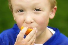 Ung pojke som äter en orange yttersida Arkivbild