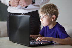 Ung pojke som använder faders dator royaltyfria foton