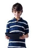 Ung pojke som använder minnestavladatoren. Isolerat. Arkivbilder