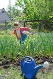 Ung pojke som arbetar i veggieträdgården Royaltyfri Fotografi