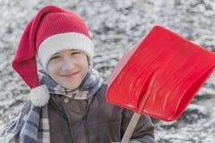 Ung pojke som bär skyffeln för snö för santa hatt den hållande övre Royaltyfria Bilder