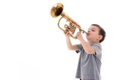 Ung pojke som blåser in i en trumpet arkivbilder
