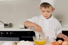 Ung pojke som bryter ägg in i en plastbunke Royaltyfri Foto