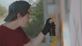 Ung pojke som drar i hemlighet färgrika grafitti på gataväggen 4K lager videofilmer