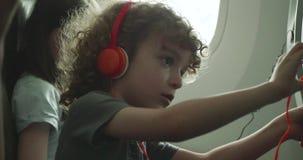 Ung pojke som försöker att justera hans apparat för enterntaiment för platsbaksida på ett flygplan stock video