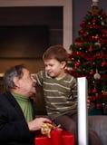 Ung pojke som får julgåva från farfar Arkivbild