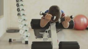 Ung pojke som gör den tunga hantelövningen för biceps lager videofilmer