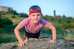 Ung pojke som gör push-UPS på en vagga Fotografering för Bildbyråer