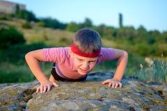 Ung pojke som gör push-UPS på en vagga Arkivfoto
