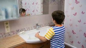 Ung pojke som gör ren hans tänder i badrummet stock video