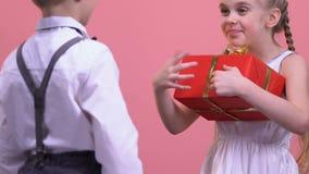 Ung pojke som ger gåva till den lyckliga förvånade flickan, beröm, födelsedagparti arkivfilmer