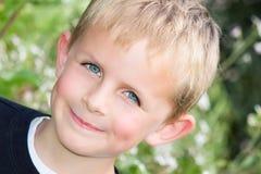 Ung pojke som grinar i trädgården Arkivbild