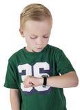 Ung pojke som håller ögonen på tiden på hans armbandsur Fotografering för Bildbyråer