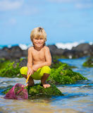 Ung pojke som har gyckel på den tropcial stranden Fotografering för Bildbyråer