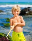Ung pojke som har gyckel på den tropcial stranden Arkivfoton