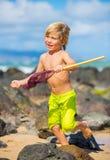 Ung pojke som har gyckel på den tropcial stranden Royaltyfria Foton