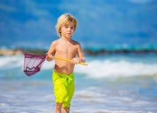 Ung pojke som har gyckel på den tropcial stranden Arkivfoto