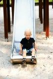 Ung pojke som har gyckel på en glidbana Arkivfoto