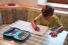 Ung pojke som hemma studerar Arkivbilder