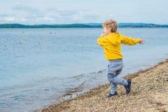 Ung pojke som kastar stenar i havsvatten Arkivfoto