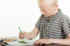 Ung pojke som koncentrerar på hans målning Royaltyfria Foton