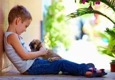 Ung pojke som kramar den lilla valpen Royaltyfri Fotografi