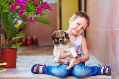 Ung pojke som kramar den lilla valpen Arkivbilder