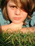 Ung pojke som lägger i gräs Arkivfoto