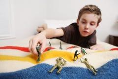 Ung pojke som lägger på hans säng som spelar med leksaksoldater royaltyfri foto