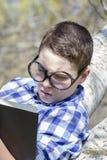 Ung pojke som läser en bok i träna med grunt djup av fältet fotografering för bildbyråer