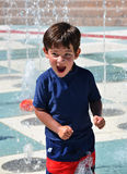 Ung pojke som leker i vattnet Arkivbilder