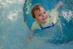 Ung pojke som ler, som han spelar i en pöl royaltyfri foto