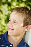 Ung pojke som ler i trädgården Fotografering för Bildbyråer
