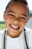 Ung pojke som ler med hängslen Arkivbilder