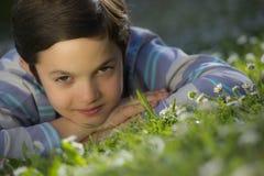 Ung pojke som ligger i gräset Arkivbilder