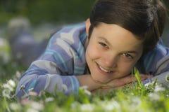Ung pojke som ligger i gräset Royaltyfri Foto