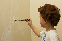 Ung pojke som målar en vägg i en lokal Royaltyfri Foto