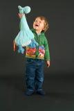 Ung pojke som poserar med ett välfyllt djur Arkivfoton