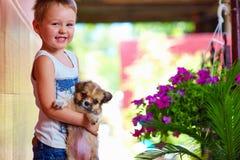 Ung pojke som rymmer den lilla valphunden Arkivbild