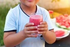 Ung pojke som rymmer sunt exponeringsglas av vattenmelonsmoothien royaltyfria bilder