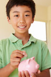 Ung pojke som sätter pengar i piggybank Arkivbild