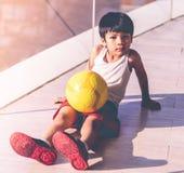 Ung pojke som sitter med fotboll p? golvet royaltyfri foto