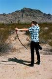 Ung pojke som skjuter en pilbåge och en pil Fotografering för Bildbyråer