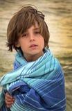 Ung pojke som slås in upp på stranden Royaltyfria Bilder