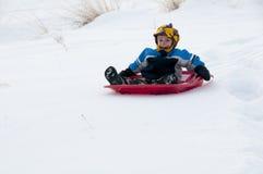 Ung pojke som sledding i snow Arkivbild