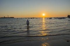 Ung pojke som slickar deras fot på stranden på solnedgången Arkivfoto