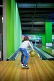 Ung pojke som spelar att bowla inomhus Royaltyfri Bild