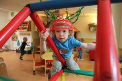 Ung pojke som spelar i en creche (barnkammaren) arkivfoton